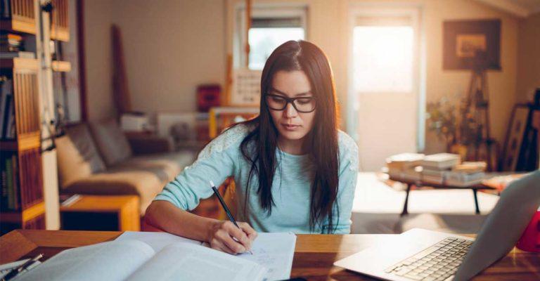 Garota de cabelo comprido escrevendo em um caderno, estudando inglês