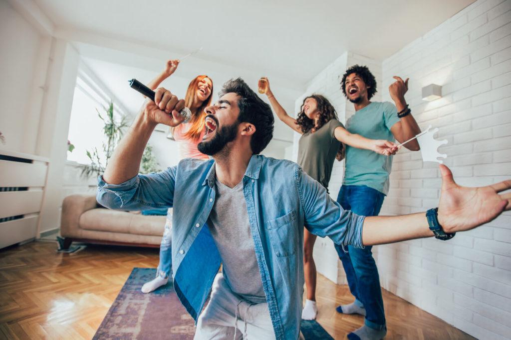 Amigos cantando em uma sala, num videoke, treinando inglês em casa