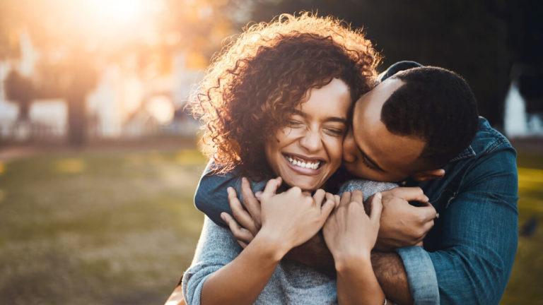 Homem abraçando uma mulher e dando um beijo no rosto dela