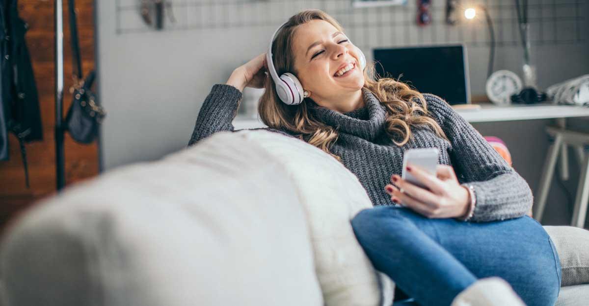 Mulher deitada no sofá e com fone de ouvidos ouvindo podcasts em inglês