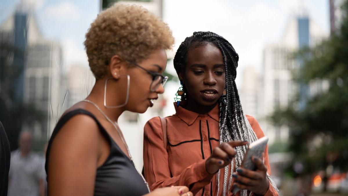 Duas amigas olhando o celular e estudando verbos auxiliares