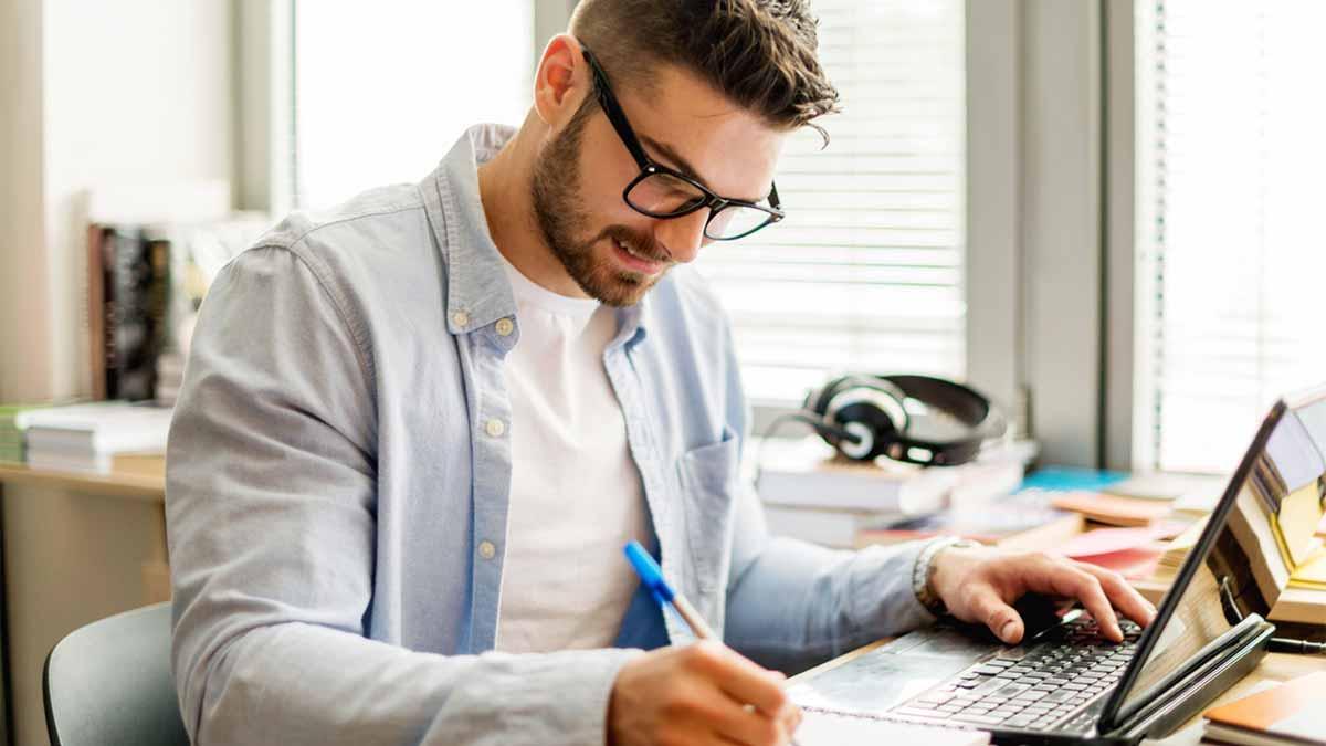 Homem estudando com um caderno os verbos em inglês mais utilizados