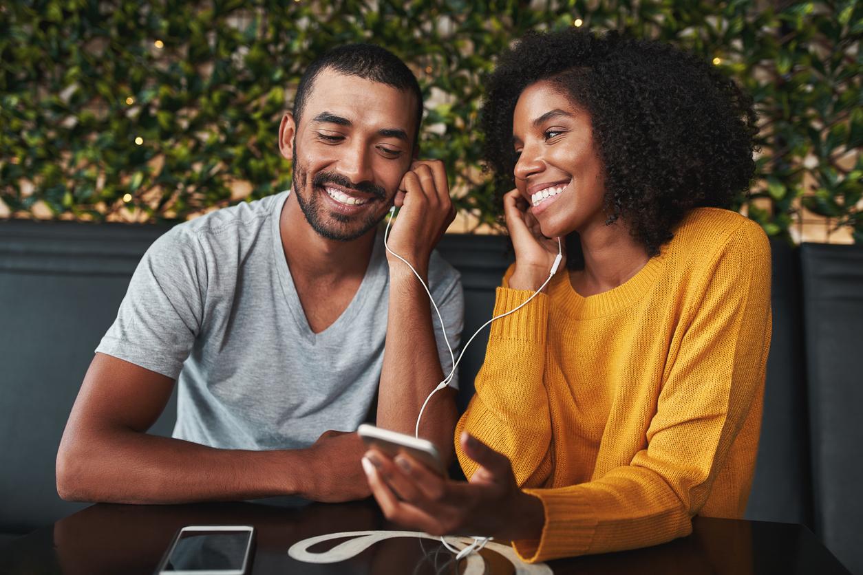 Casal ouvindo música romântica em inglês cada um com um lado do fone de ouvido