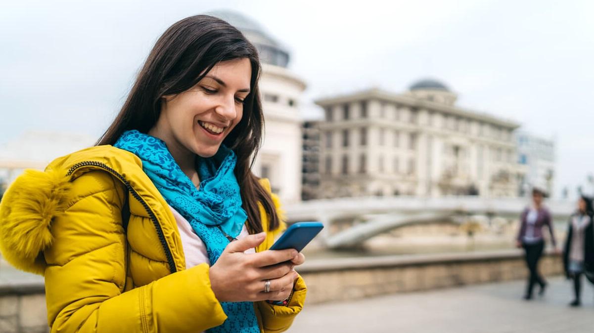 Garota de cabelo comprido escuro e jaqueta amarela com celular na mão enviando frases em inglês