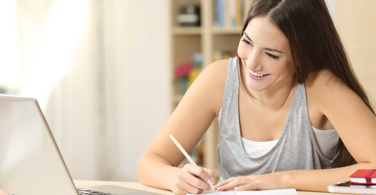 Mulher sentada em uma mesa de estudos, olhando o computador e fazendo anotações no caderno