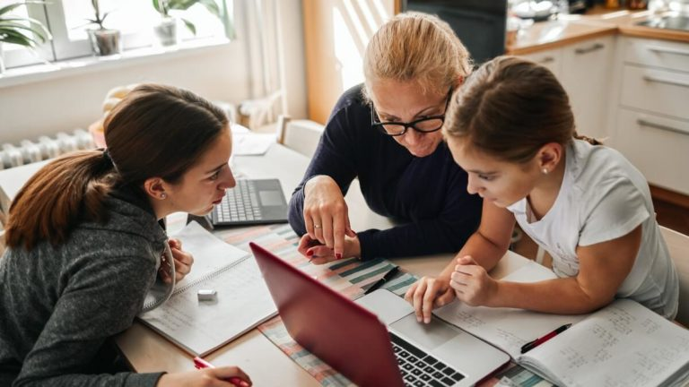 Uma mulher mais velha, uma jovem e uma criança estudando em uma mesa com um notebook e alguns livros abertos