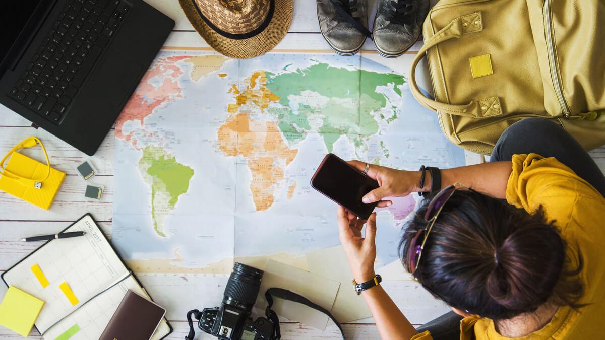 viajante vendo o celular e sobre um mapa