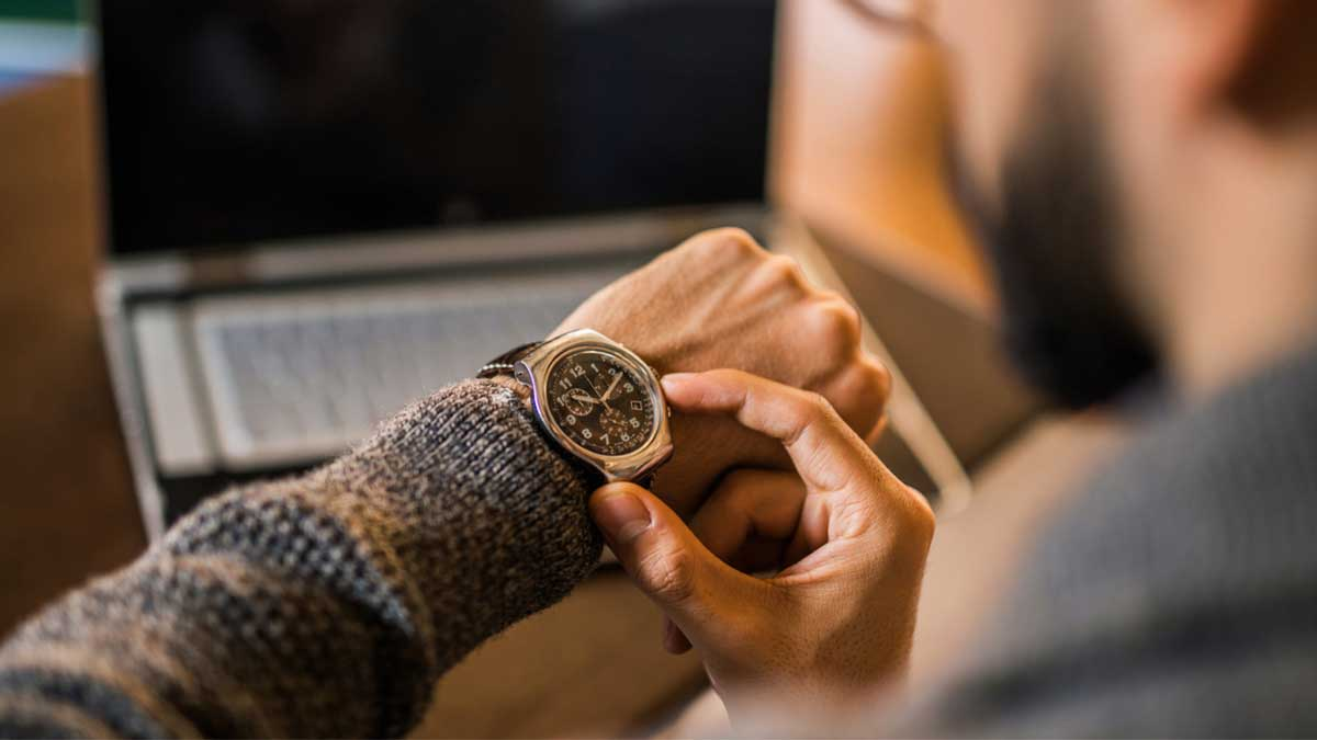 Homem olhando as horas em seu relógio