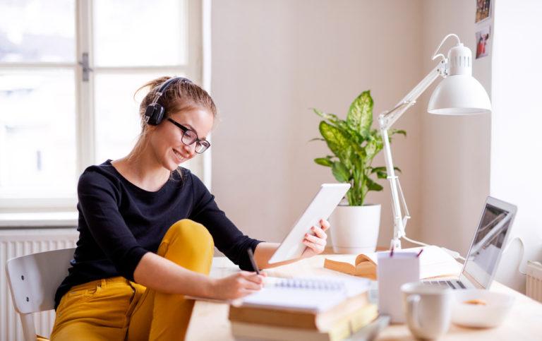 Mulher jovem, com fones de ouvido e caderno na mão, fazendo anotações enquanto estuda