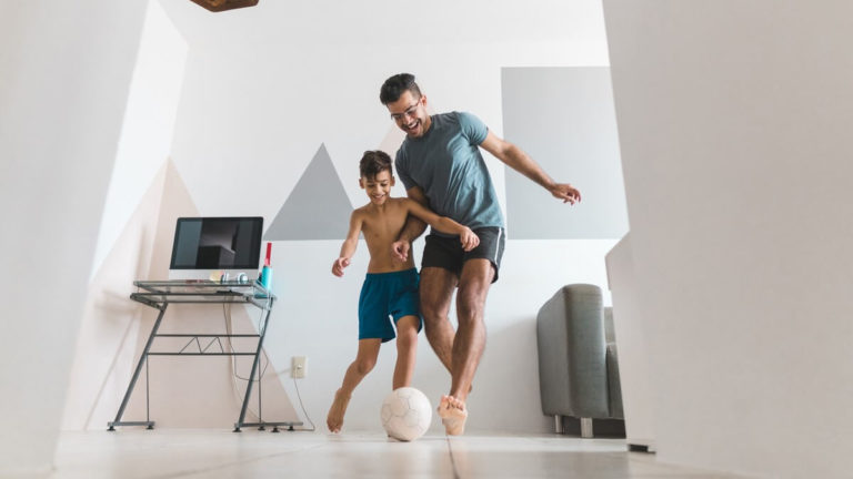 Pai e filho jogando futebol dentro de uma sala
