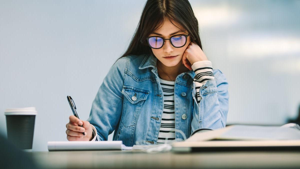 Menina sentada e estudando com alguns livros