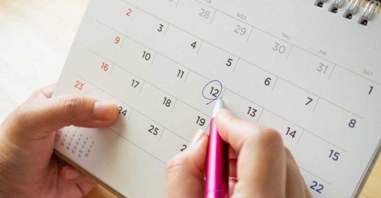 Uma mão feminina segurando um calendário e circulando uma data em inglês