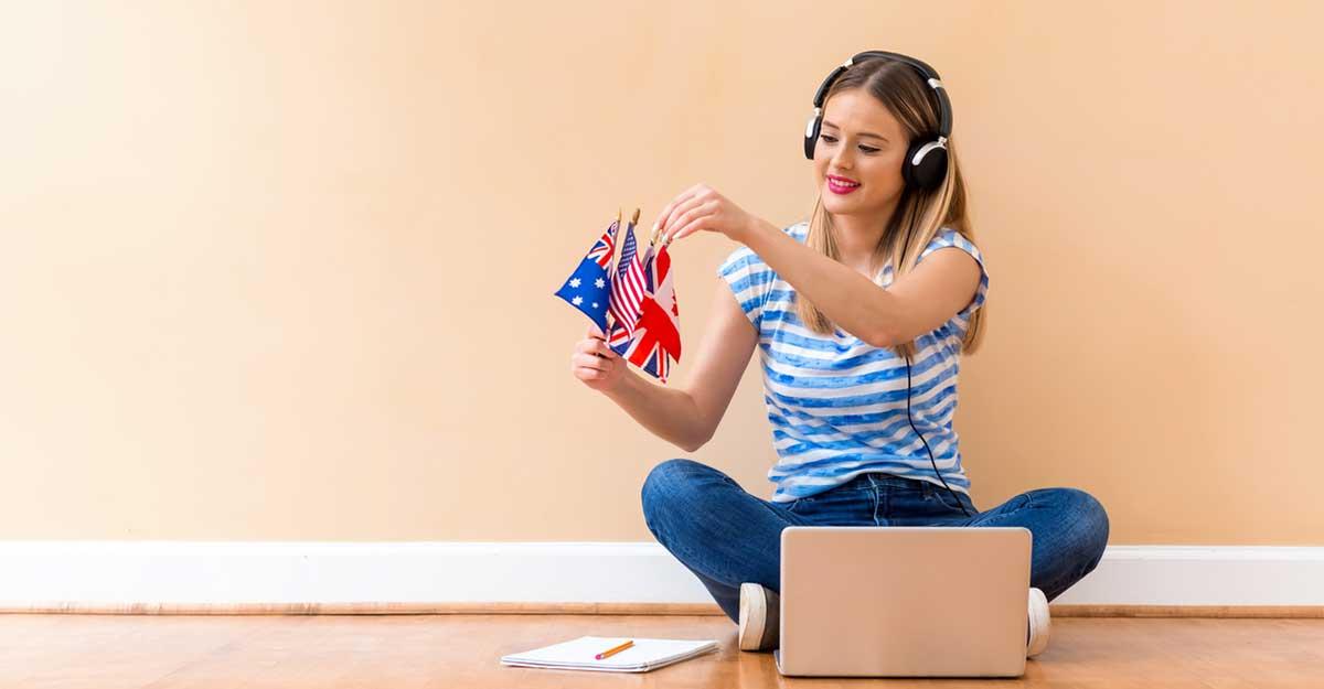 Mulher jovem sentada no chão com um computador e segurando três pequenas bandeiras