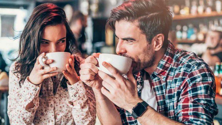 Casal composto por homem e mulher se olhando enquanto cada um toma uma xícara de chá
