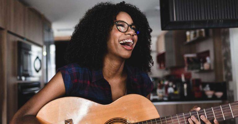 Mulher tocando no violão músicas em inglês