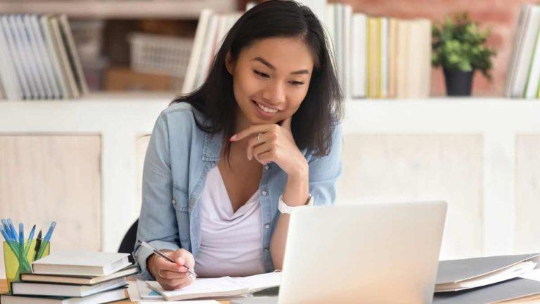 Mulher olhando a tela do notebook e fazendo anotações