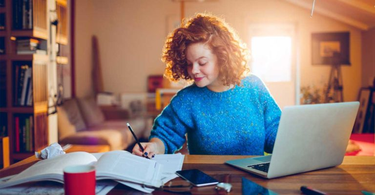Mulher sentada numa mesa, com computador e cadernos a sua frente, indicando que está estudando textos em inglês