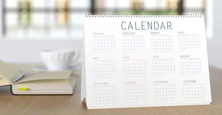 Uma folha de calendário com os meses em inglês em cima de uma mesa com livros