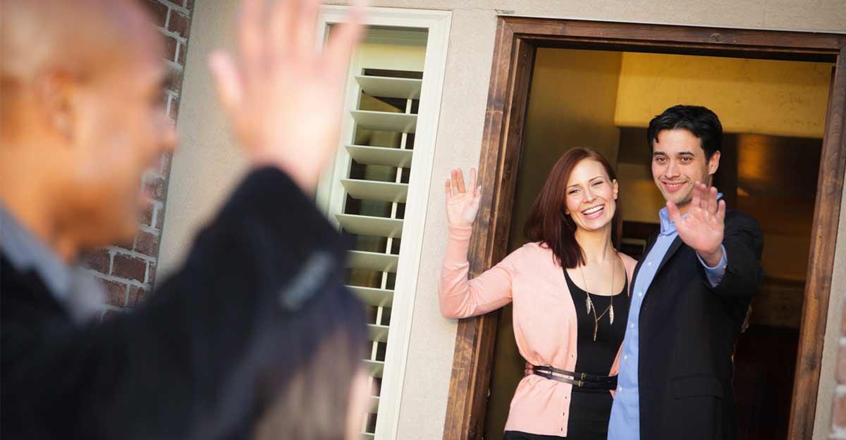 Casal na porta de casa se despedindo de um amigo