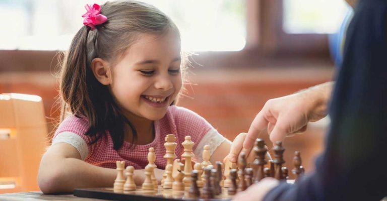 Menina brincando de jogar xadrez