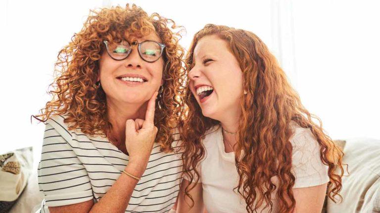 Mãe e filha sentadas no sofá e rindo ao assistir televisão