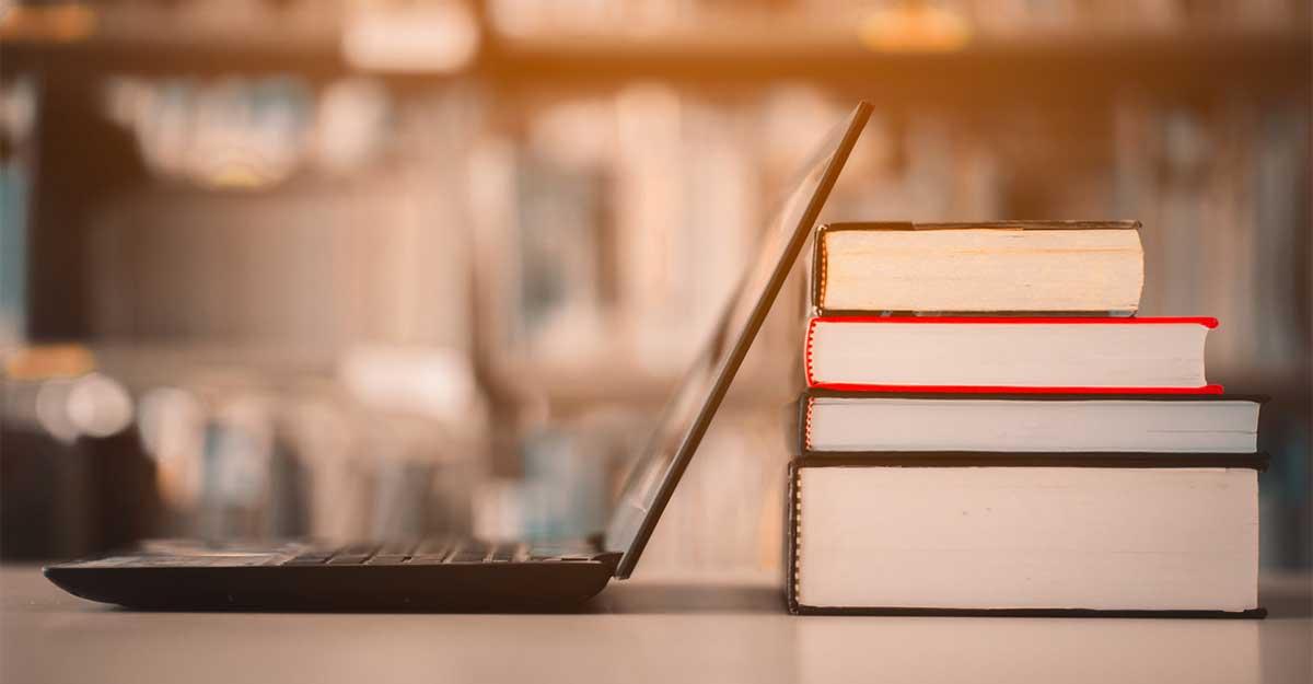 Notebook encostado em três livros