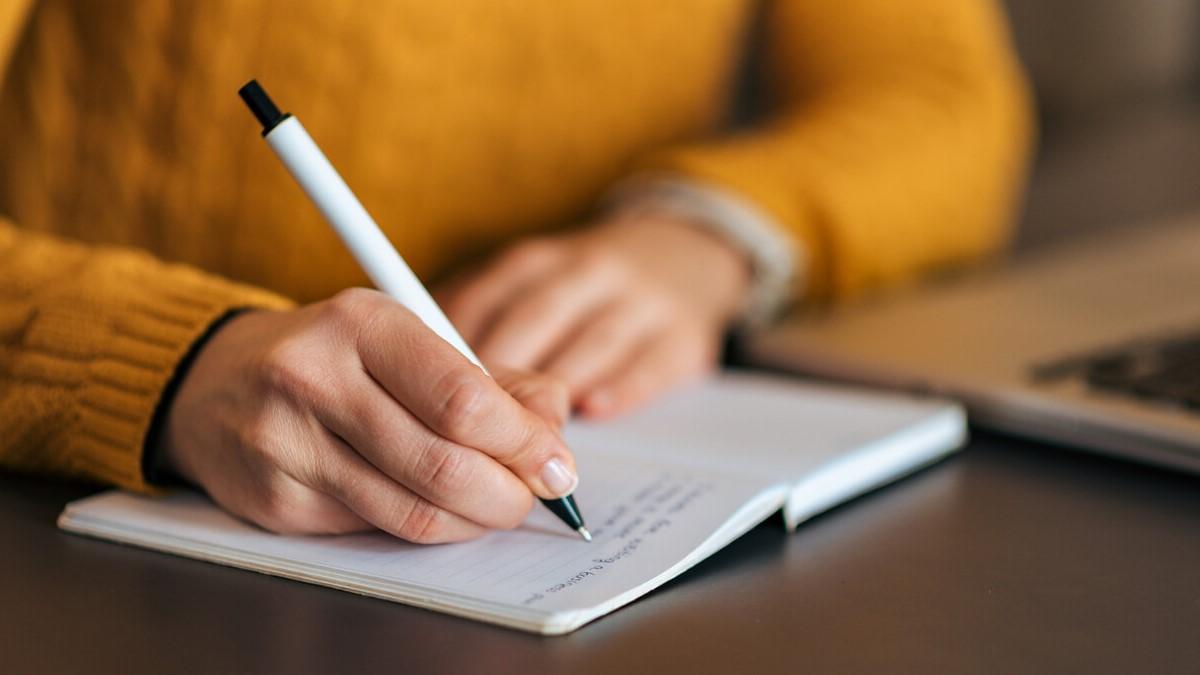 mão feminina fazendo anotações em um caderno