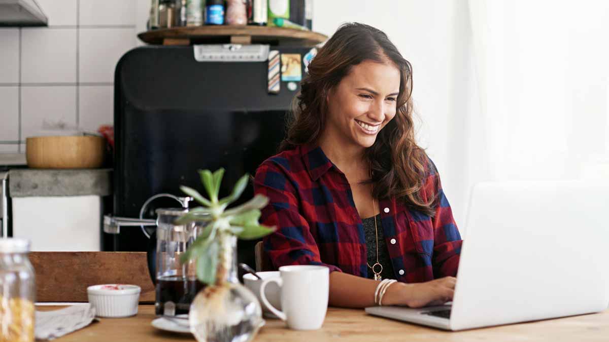 Garota em uma mesa de estudos, com um computador e uma xícara de café. Ela busca por superlativos em inglês
