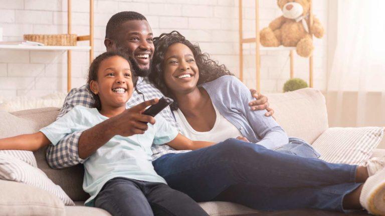 Família composta por um homem, uma mulher e uma menina, sentados sorrindo no sofá e o homem segura um controle remoto