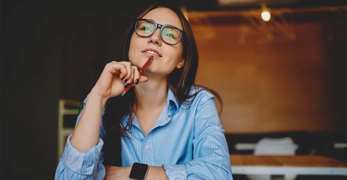 Garota com a caneta encostada no rosto com expressão de dúvida