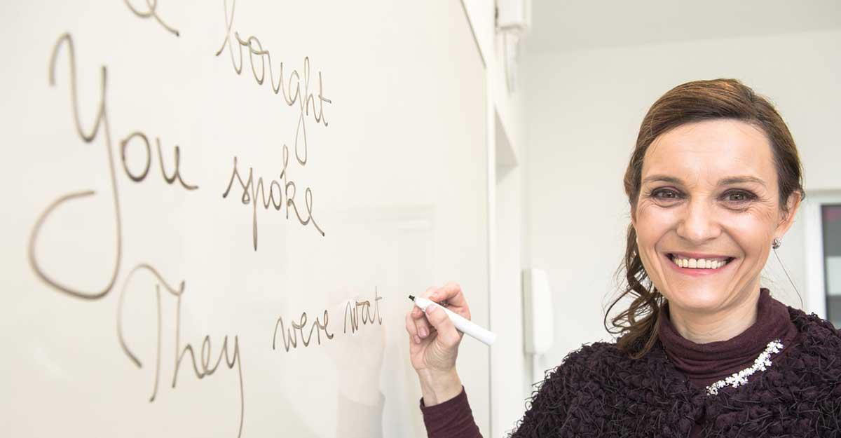 Professora fazendo anotações sobre present continuous na lousa
