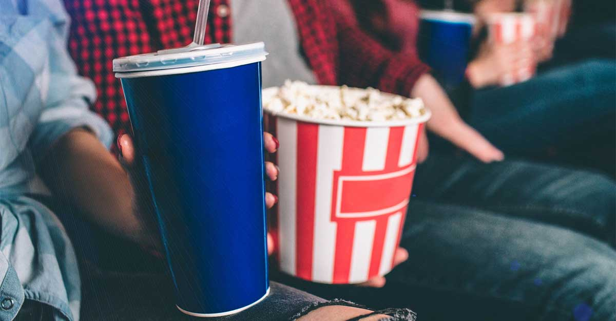 Imagem de um pote e pipoca e um copo de refrigerante de cinema