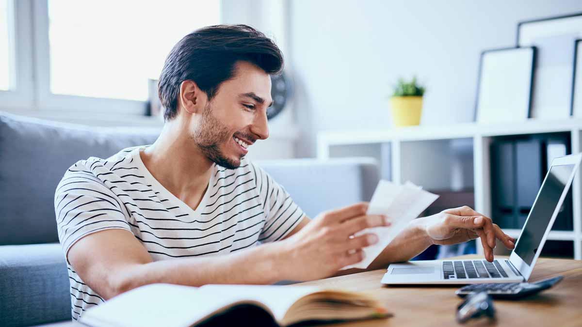 Homem jovem estudando os adjetivos e pronomes possessivos com alguns cadernos em um mesa