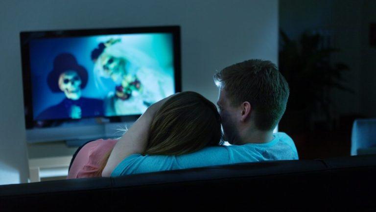 Um homem e uma mulher sentados em um sofá olhando para a TV que passa um filme de terror