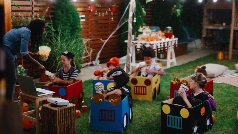 Diversas crianças em caixas grandes em uma festa com a temática de Halloween