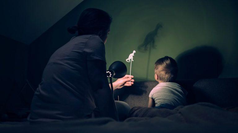 Mãe sentada com o filho em uma cama e com uma lanterna apontada em direção a parede, fazendo sombra de um boneco de dinossauro que ela tem nas mãos