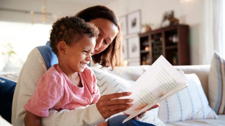 Mãe sentada em um sofá e segurando seu filho no colo enquanto lê um livro pra ele