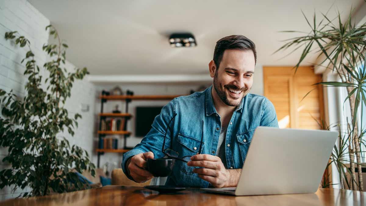 Homem estudando inglês com o computador da mesa e uma xícara de café ao lado