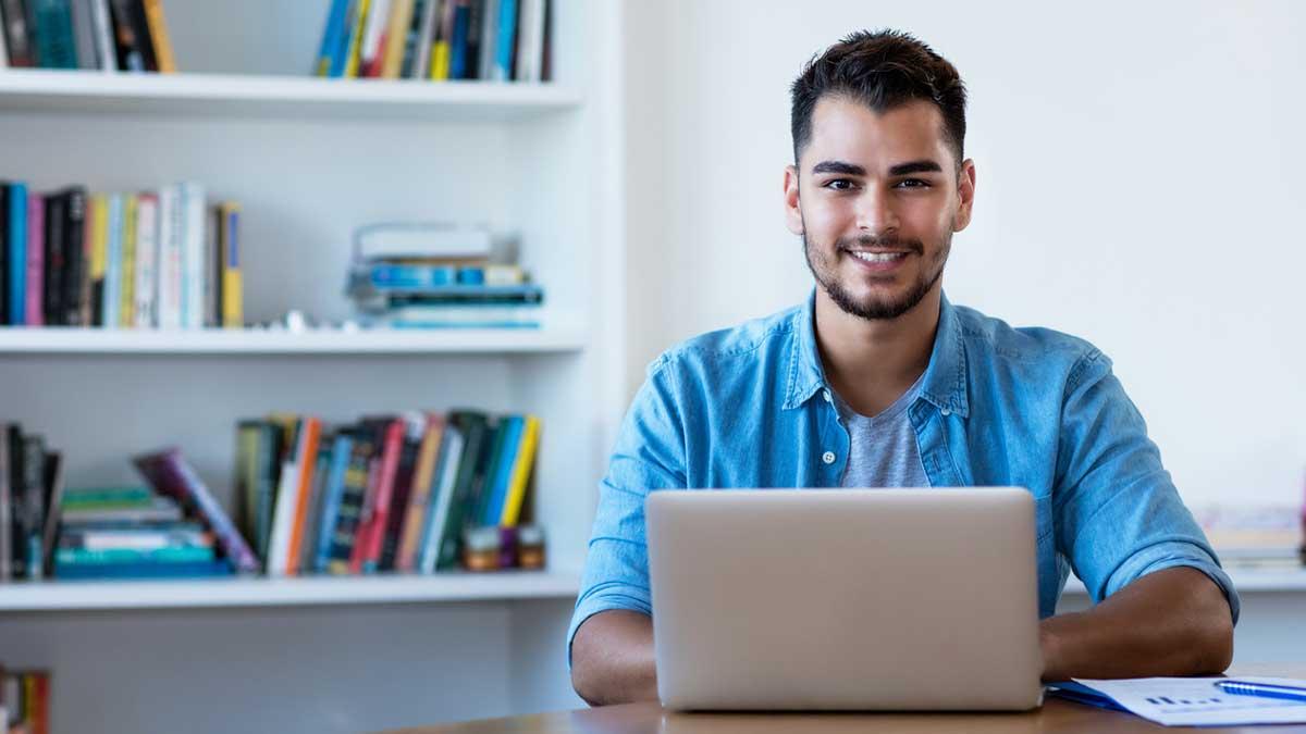 Homem com cabelo moreno sentado numa mesa e digitando em um notebook
