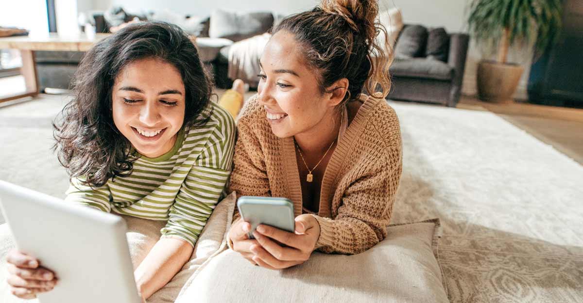 Amigas olhando uma tela e sorrindo