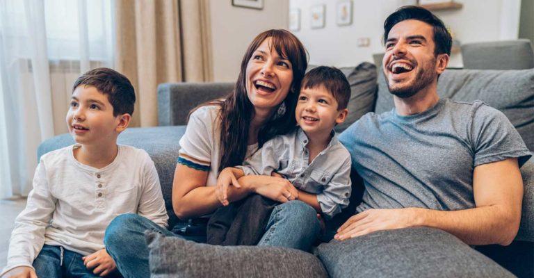 Família sentada no sofá assistindo a filmes em inglês
