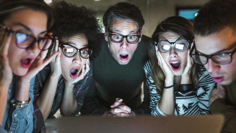 5 amigos olhando para uma tela e com cara de espantados