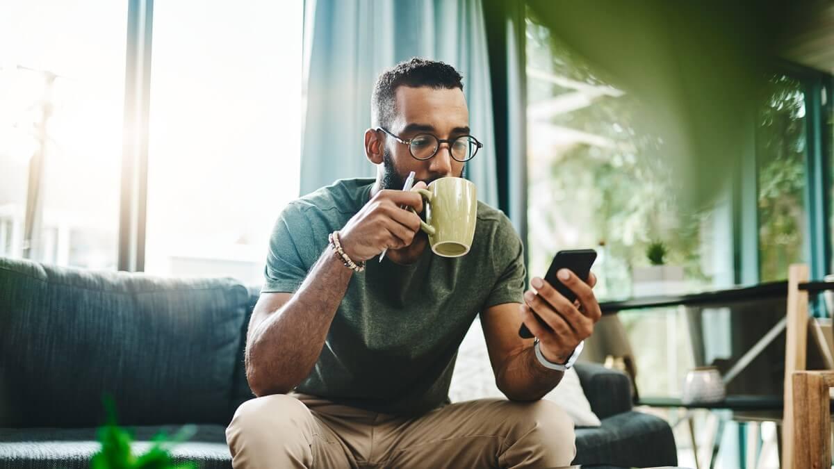 Homem jovem sentado no sofá, com uma caneca na mão e o celular em outra