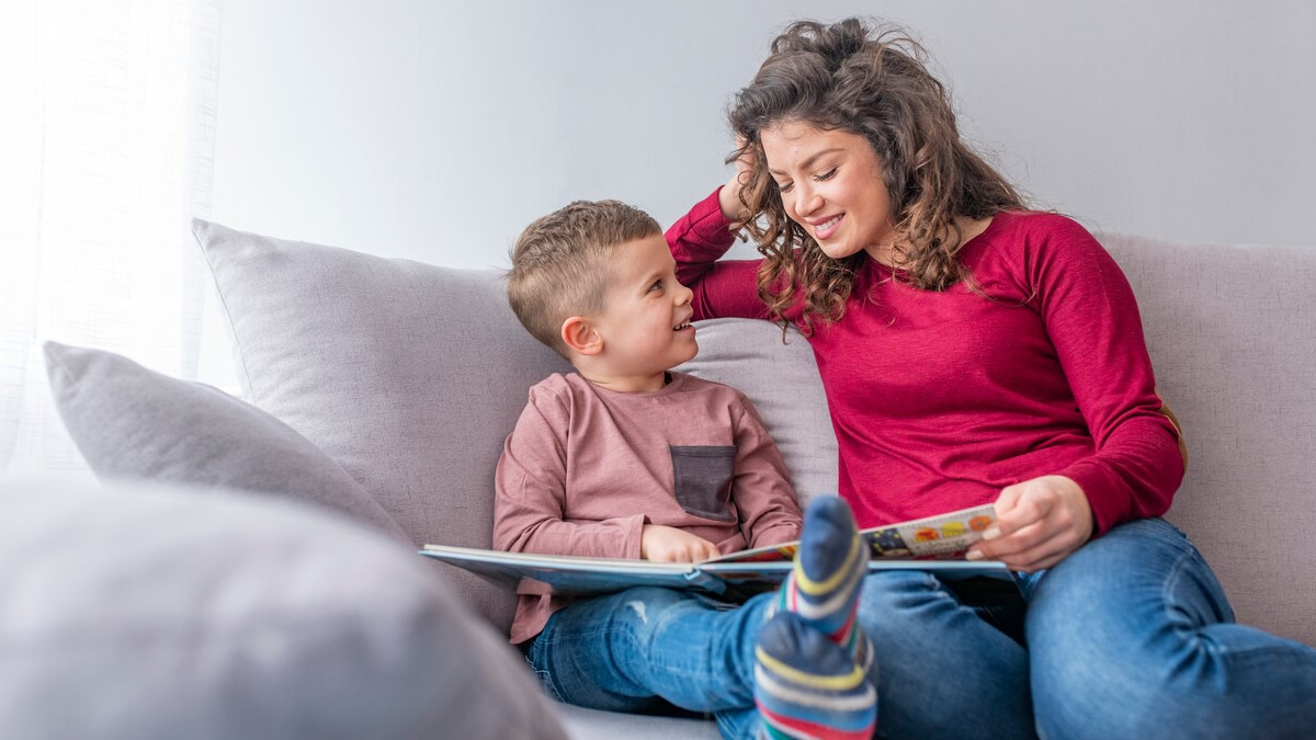 Mãe e filho sentados no sofá com um livro no colo