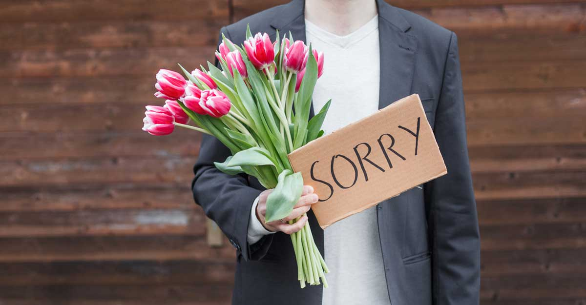 """Homem segurando uma placa escrito """"Sorry"""" e flores na mão"""