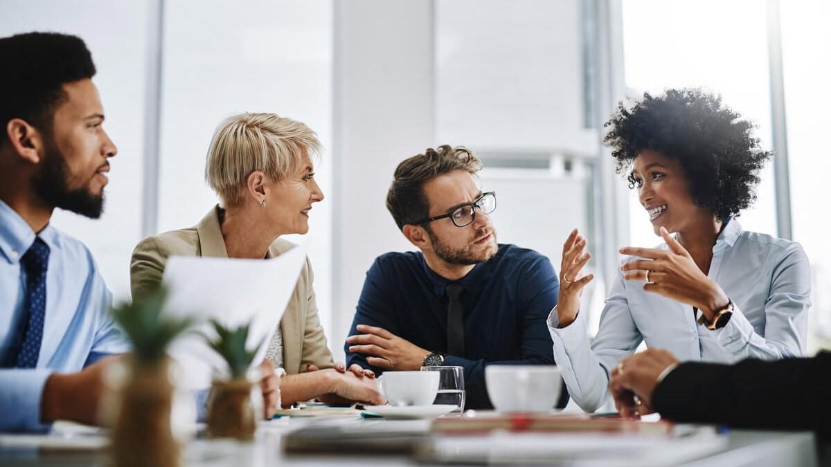Quatro pessoas sentadas em volta de uma mesa fazendo uma reunião de trabalho