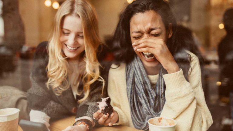 Duas amigas gargalhando após ouvirem uma piada ruim
