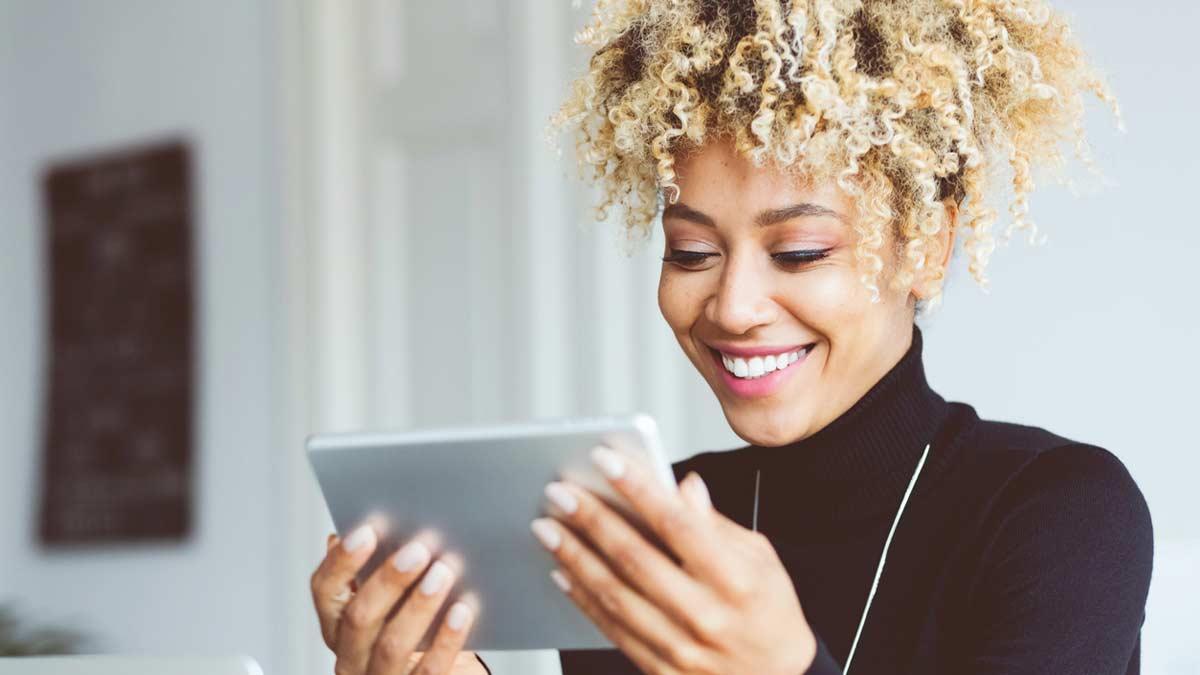 Mulher negra de cabelo cacheado loiro, segurando um tablet, olhando para ele com fones de ouvido e sorrindo