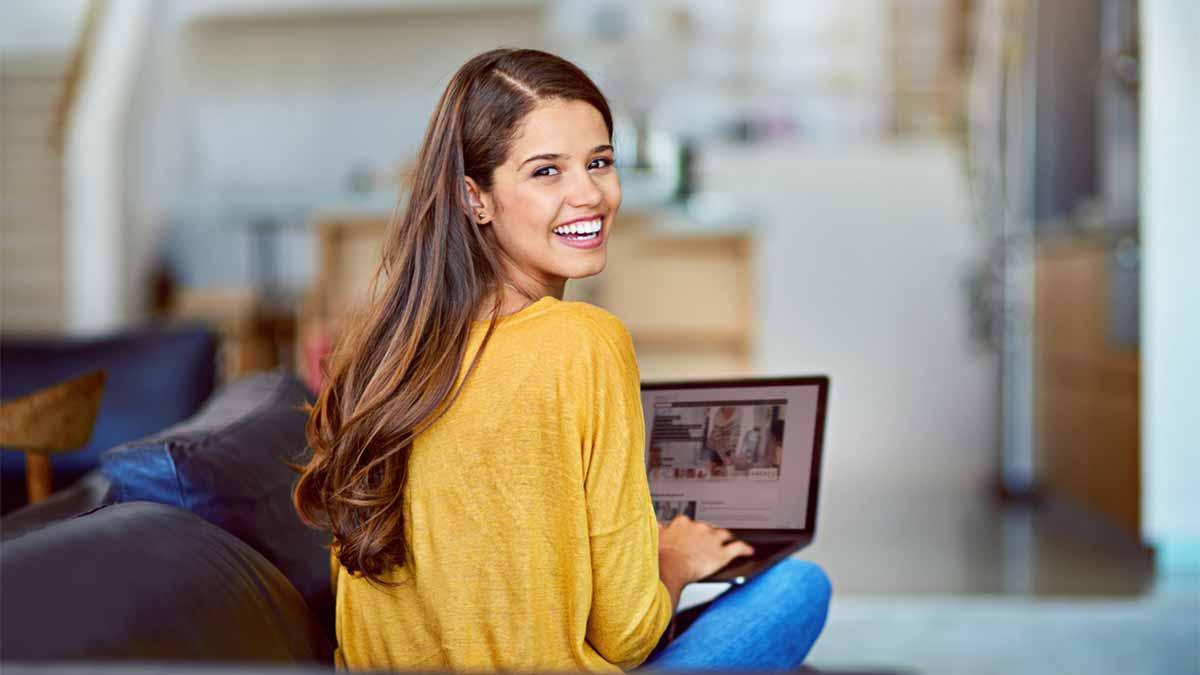 Mulher morena sentada de costas olhando para trás e segurando um notebook
