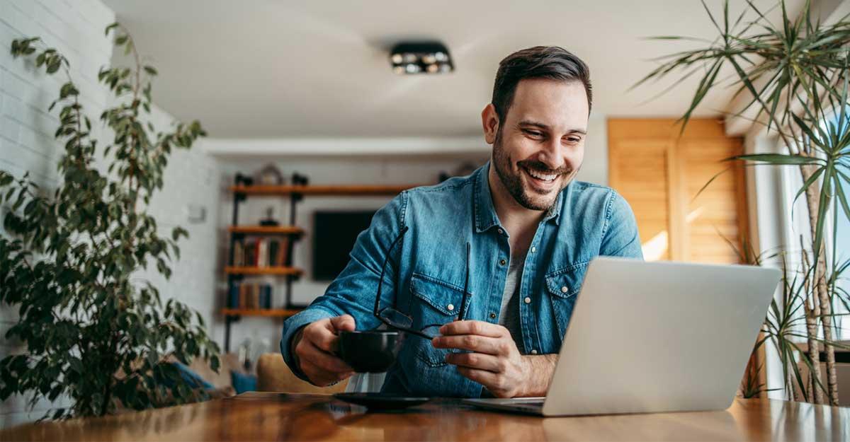 Homem estudando as collocations em inglês em uma mesa com um notebook e uma xícara de café